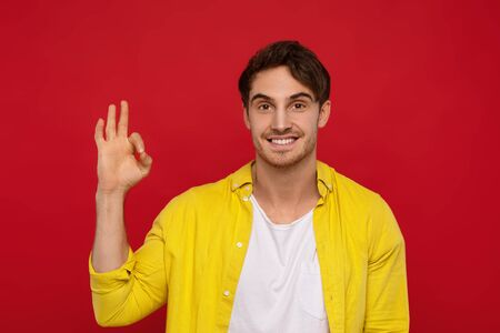 Yeah, its ok. Positive handsome man in yellow shirt showing ok sign with one hand, has big smile, being in high spirit, isolated on red background