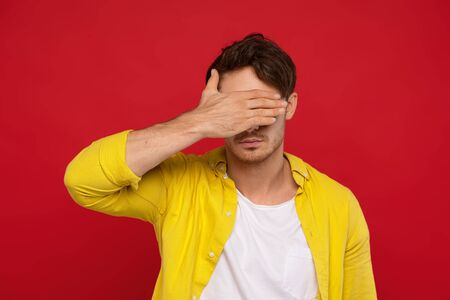 handsome man in yellow shirt covering face with hand isolated on red background