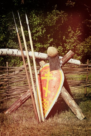 rus: Samara, Russia, the festival of historical reconstruction  ancient Russia ages 11-13 - August 11, 2013 - three spears, a shield with an Orthodox cross with a helmet and chain mail about wicker fence on the field near the forest