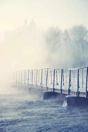 evaporacion: viejo puente sobre el río en una mañana helada con la evaporación de las aguas de fondo - la silueta de las cúpulas de la iglesia