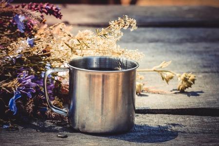 tea filter: steel mug of tea on the table and fresh flowers, filter