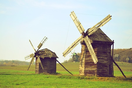 damaged roof: two old wooden windmills with a broken roof on a green field Stock Photo