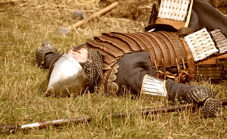 Samara, Russia, the festival of historical reconstruction ancient Russia ages 11-13 - August 16, 2013 - : man in the armor of ancient warrior lying on the ground