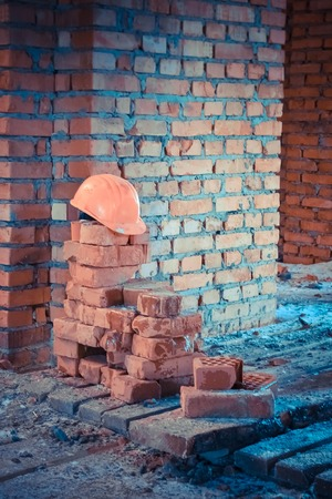 lies: Orange helmet lies on the bricks at a construction site Stock Photo