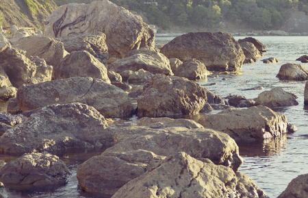 black giant mountain: abstract background of huge stones on the shore, filter Stock Photo