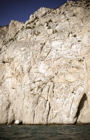 cusp: sheer stone cliff on a sunny day near the water, Crimea, filter