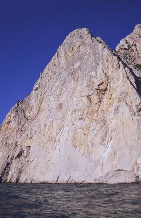 unyielding: triangular flat rock above the sea, filter