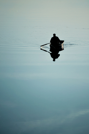 windless: one man in a small boat sailing boat on the lake river rowing oars. River with a smooth mirror surface of the water. Weather quiet, calm, windless