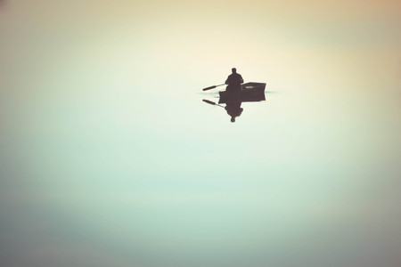 un homme dans un petit bateau bateau à voile sur le lac avirons de la rivière. Rivière avec une surface lisse comme un miroir de l'eau. Météo calme, apaisant, windless