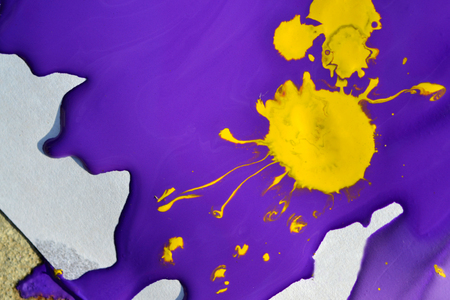improvisation: violet gouache paint and a yellow blotch in the middle close-up. Abstract background purple and yellow liquid paint. Artistry, art, creativity, Stock Photo