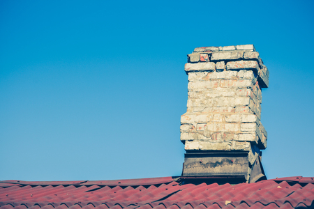 dilapidation: old brick chimney on the roof for the smoke against the clear sky