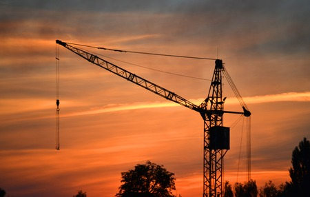 black silhouette of a construction crane at dusk, dawn and clouds in the sky