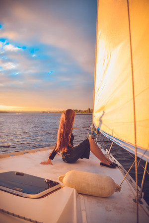 stern: girl with long brunette hair sitting at the stern of the yacht and looks into the distance at sunset, sunrise