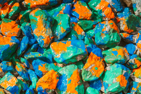 Pebbles painted bright colored paint. Stony surface covered with different colors. Abstract flat line background.