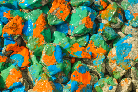 originative: Pebbles painted bright colored paint. Stony surface covered with different colors. Abstract flat line background.
