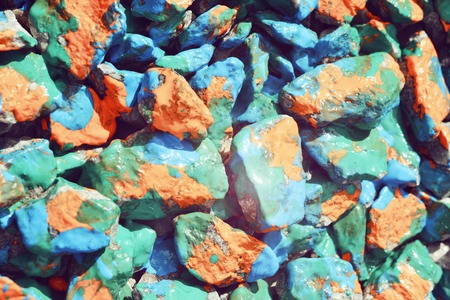 stony: Pebbles painted bright colored paint. Stony surface covered with different colors. Abstract flat line background.