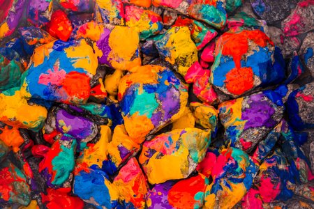 colorific: Pebbles painted bright colored paint. Stony surface covered with different colors. Abstract flat line background.