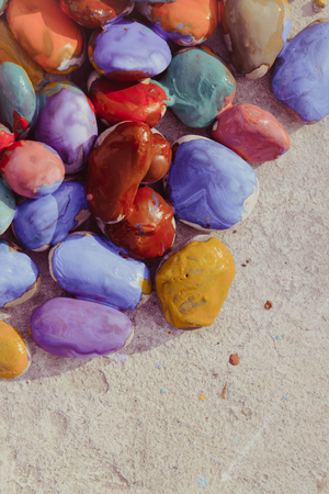 phantasy: Colored stones colored paints in different colors lie on a flat surface. Second half empty. Close-up