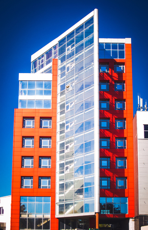 idealistic: facade, front of the large house red and gray in the high-tech style on a bright sunny day on blue sky background