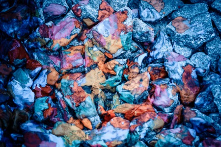 phantasy: abstract background of the plane lying on colored stones close-up,. Many stones painted with colored inks