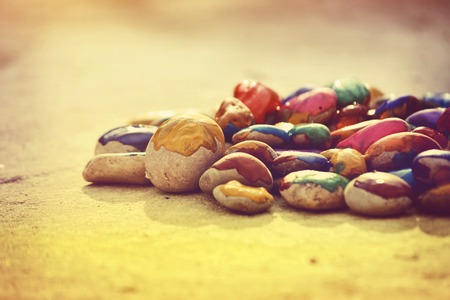 improvisation: Many small pebbles covered with multicolored paint lie on the surface close-up