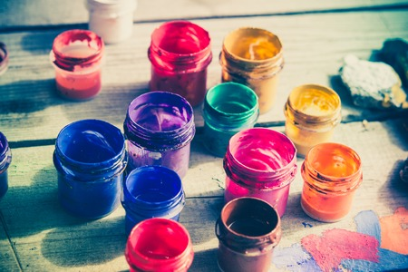 artistry: many small paint jars with different colors on a wooden surface, open jars and lids are close. Creative, virtuosity, artistry