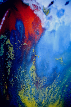 bursts of multicolored paints and mixed together white paper. Drawn splashes of paints of different colors on white surface. Blue, yellow, red, green color. Spreading spraying flow leak stream mixing Stock Photo