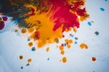 divorces and paint drips red, orange, yellow, blue blurred abstract background on a white paper background plane surface close-up macro with filter toning effect Stock Photo
