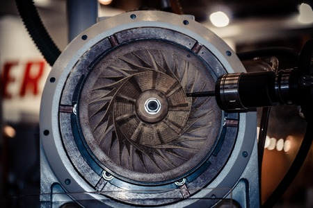 displacement: Five-axis machine for the processing of basic parts at high speeds during milling. The machine for the treatment of avia, air turbine closeup. Milling machine carves turbine blades close-up Stock Photo