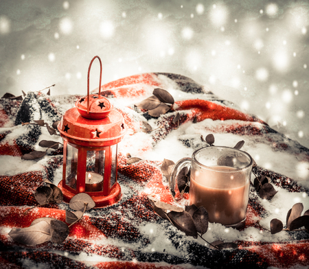 originative: Festive red candle in a lantern and a mug of coffee on a red rug with snow with green leaves. Winter snow Christmas New Year holiday background snowy winter filter
