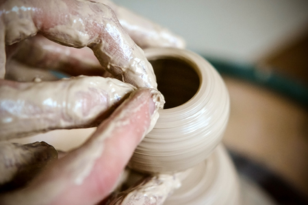 Girl sculpts in clay pot closeup. Modeling clay close-up. Caucasian man making vessel daytime of white clay in fast moving circle. Art, creativity. Ukraine, cultural traditions. Hobbies