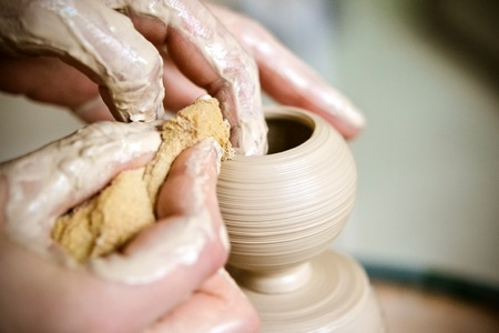 modeling clay: Girl sculpts in clay pot closeup. Modeling clay close-up. Caucasian man making vessel daytime of white clay in fast moving circle. Art, creativity. Ukraine, cultural traditions. Hobbies