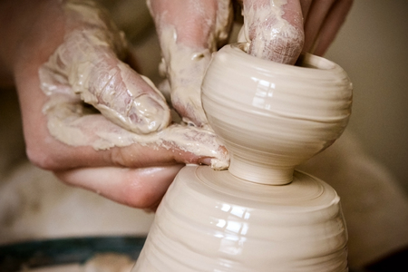 A man with his hands dub wall jug, which he sculpts out of clay on a circle. Create clay vessel. Modeling white-clay, shaping vessel. Caucasian man making vessel Cclay in circle.