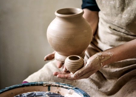 Sculpt Man potter holds palms just made pitchers of different sizes. Potter holds made pots. Workshop pottery. Ceramic skills. Sculptor sculpts products from white clay. Ukraine, national traditions Stock Photo