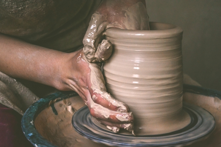 potters wheel: Creating a jar or vase of white clay close-up. Master crock. Man hands making clay jug macro. The sculptor in the workshop makes a jug out of earthenware closeup. Twisted potters wheel.