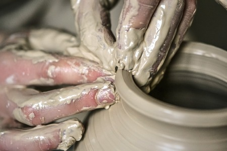 Hands in the clay macro. Making Crock crude wet close-up. Man hands making clay jug macro. The sculptor in the workshop makes a jug out of earthenware closeup. Vase of white clay crude wet closeup, Stock Photo