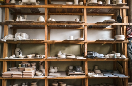 Wooden racks in a pottery workshop in which there are pottery, many different pottery standing on the shelves in a potery workshop. Low light Stock Photo
