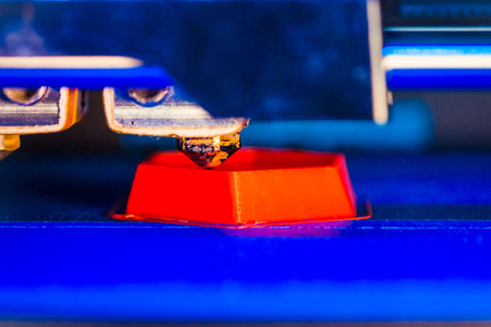 3d printer printing red faceted geometric shapes on a blue background close-up. Bright contrast image automatic three dimensional 3d printer performs plastic modeling in laboratory.