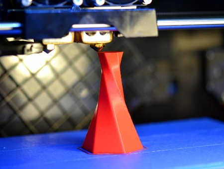 3D printer printing isolated volume triangular object red color on the basis of blue and black background close-up. Modern 3d printing technology Standard-Bild