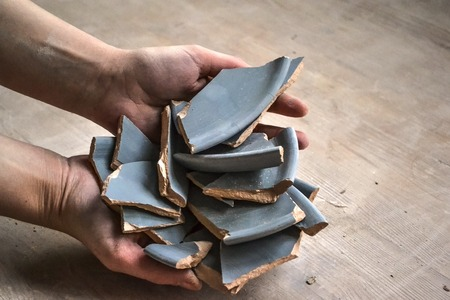 smithereens: In hand debris or smithereens. Ware splinters in hands closeup. Caucasian man holds in the hands of the debris or fragments of pottery broken plate