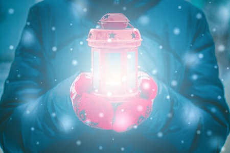 originative: Man holding a red candle lantern with a candle close up. A man dressed in a warm coat and red gloves. Winter. Falling snow, snowfall, snowflakes. Glare glow in the center