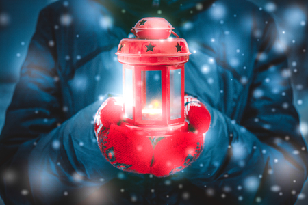 originative: Man holding a red candle lantern with a candle close up. A man dressed in a warm coat and red gloves. Winter. Falling snow, snowfall, snowflakes Stock Photo