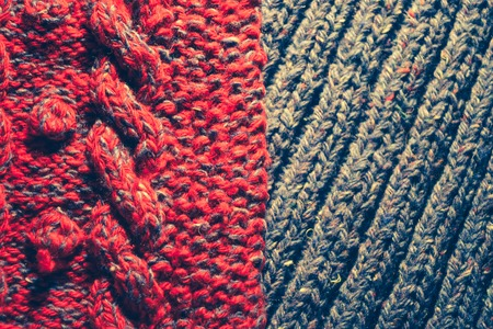 cable stitch: Background of knitting red and blue patterns, knitting wool texture background close-up, macro