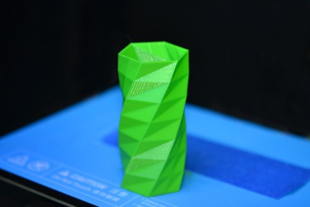 prototyping: The object printed 3D printer on a blue and black background in the 3D printer. Automatic three dimensional 3d printer performs plastic green colors modeling in laboratory.