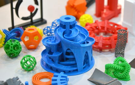 Models printed by 3d printer. Bright colorful objects printed on a 3d printer on a table Фото со стока