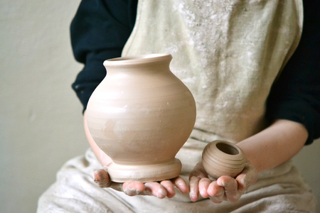Potter holds just hired by pitcher. Ceramic skills. Sculptor sculpts products from white clay. Workshop pottery.Ukraine, national traditions Stock Photo