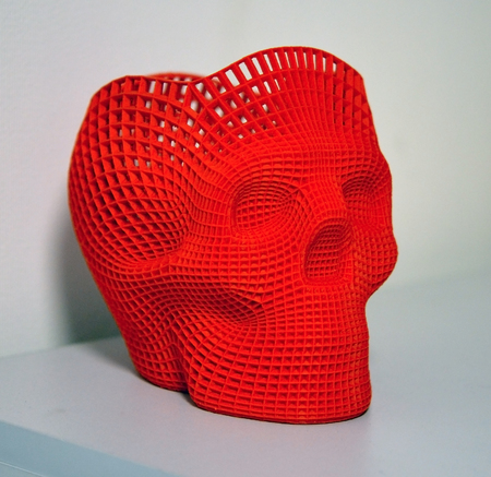 Skull printed with plastic of red color on a 3d printer.