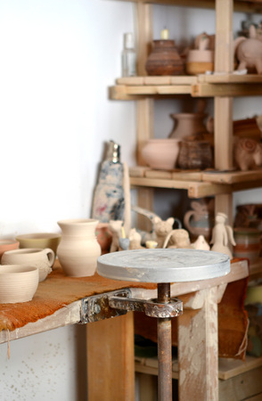 pottery manufactory, empty potters wheel, pottery from clay on the table