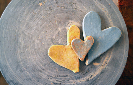 Three clay hearts painted with paints on a potters wheel top view.