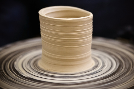 Raw clay jars pots stand and turns potters wheel in the potters workshop close. Art, creativity. Stock Photo